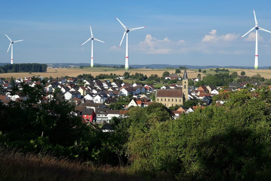 Blick über Menzingen im Hintergrund sind die geplanten Windkraftanlagen maßstabsgetreu dargestellt.